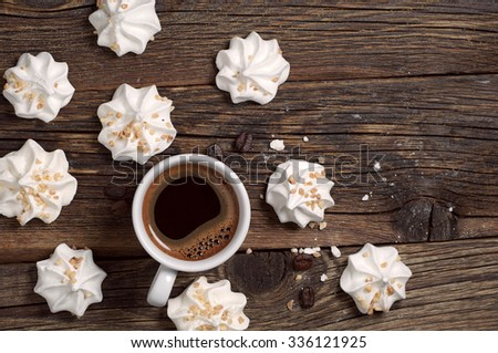 Meringue Cookies with nuts and cup of coffee on dark wooden background, top view - stock photo