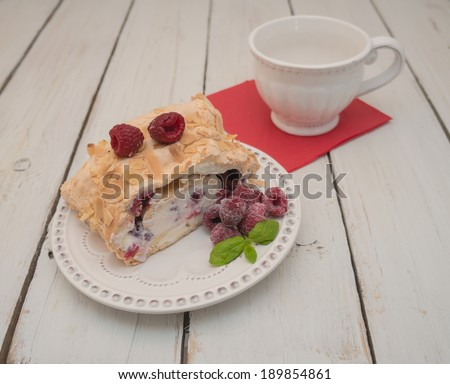 meringue roulade with cream and raspberries on wooden table