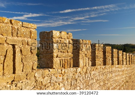 Merlons on a fortress wall, contrasting with a blue sky - stock photo