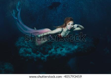 Mermaid Girl floats on the sea floor. - stock photo