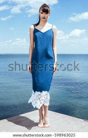 Mermaid girl in a long jeans dress wearing heels. Model at the pier over sea and sky in Summer