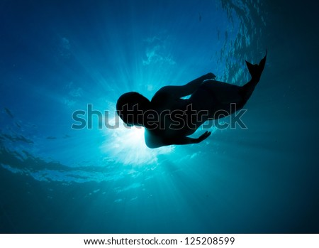Mermaid silhouette, beautiful young women free diving in the deep blue wearing a mermaid tail monofin - stock photo