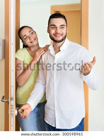 Merry beautiful couple coming to the apartment - stock photo