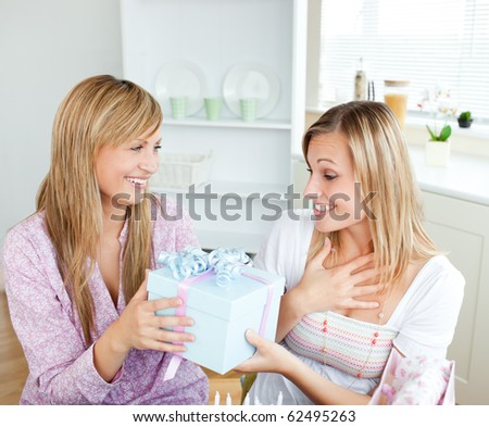 Merry caucasian woman giving a present to her surprised friend for her birthday in the kitchen at home - stock photo