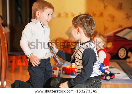 Merry children playing as doctor and patient  - stock photo