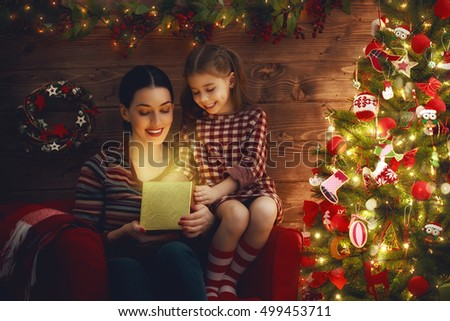 Merry Christmas and Happy Holiday! Loving family mother and child with magic gift box on Christmas.