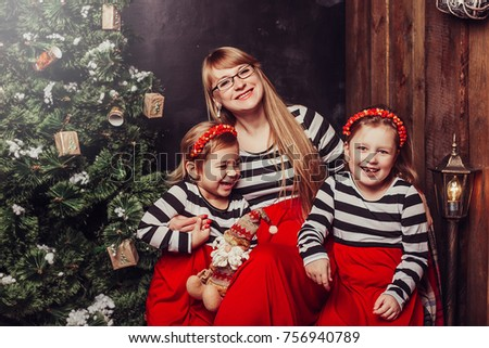 Merry Christmas and Happy Holidays! Mom and daughters near the Christmas tree indoors. The morning before Xmas. Portrait loving family close up