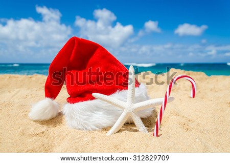 Merry Christmas and Happy New Year background with Santa Claus Hat, candy and starfish on the tropical beach near ocean in Hawaii - stock photo