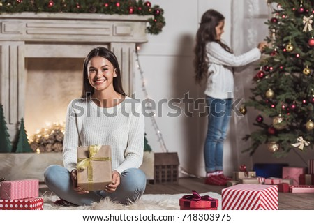 Merry Christmas and Happy New Year! Beautiful woman is holding a present, looking at camera and smiling, her daughter is decorating a Christmas tree