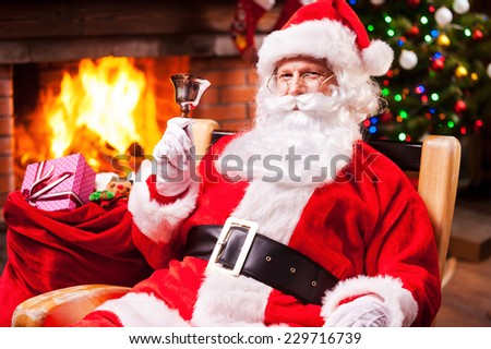 Merry Christmas and Happy New Year! Cheerful Santa Claus sitting at his chair and ringing a bell with fireplace and Christmas Tree in the background
