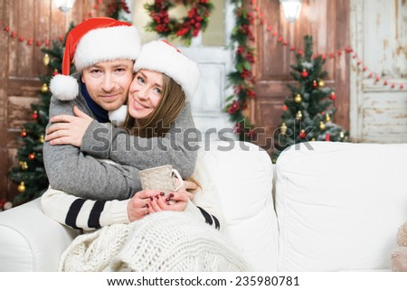 Merry Christmas and Happy New Year. Young and beautiful couple is sitting in festive New Year living room just before the Christmas.