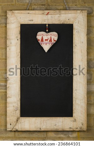 Merry Christmas and Happy New Years chalkboard blackboard heart decoration restaurant vintage menu design on painted reclaimed wooden frame, light brown brick wall, copy space