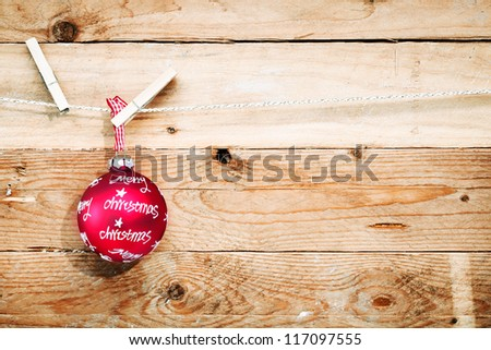 Merry Christmas background with a festive red bauble bearing a Christmas greeting hanging from a line by a peg with lots of copysapce on rough textured wooden boards - stock photo