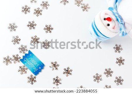 Merry Christmas background with blue greeting card and cute snowman and silver snowflakes over white.  - stock photo