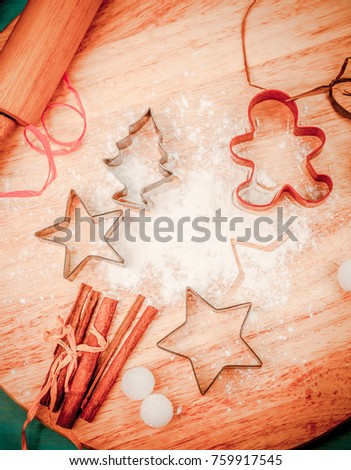 Merry Christmas baking background. Viewed from above. Raw dough for Christmas cookies, spices and star shaped cookie cutters, vintage wooden rolling pin on wooden cutting board. Winter theme