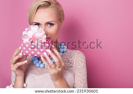 Merry christmas. Beautiful blonde woman holding small gift box with ribbon. Soft colors. Studio portrait over pink background - stock photo