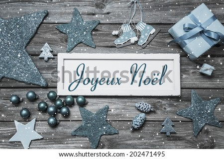 Merry Christmas card in blue and white with french text on wooden board. - stock photo