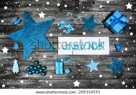 Merry christmas card or voucher. Xmas decoration in blue, white on grey wooden background with french text. - stock photo