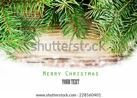 Merry Christmas Card with Fir Tree Branches on Wooden Board with Snow - stock photo