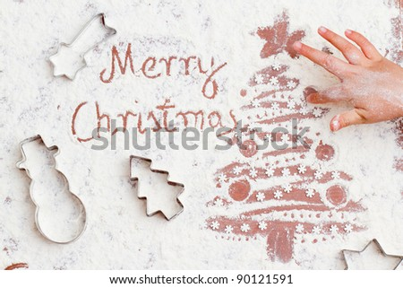 Merry Christmas -  child is painting the Christmas tree with fingers of the flour - stock photo