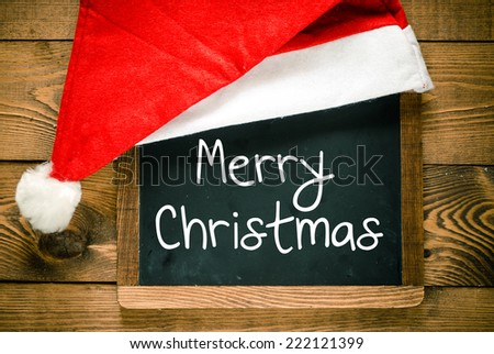 Merry Christmas. Christmas decorations with Christmas hat with place for greeting on chalk blackboard. - stock photo