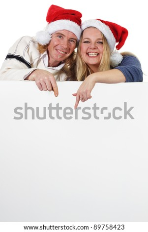 Merry Christmas couple lean on blank advertising placard - stock photo