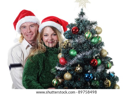 Merry Christmas Couple posing by a Christmas Tree - stock photo