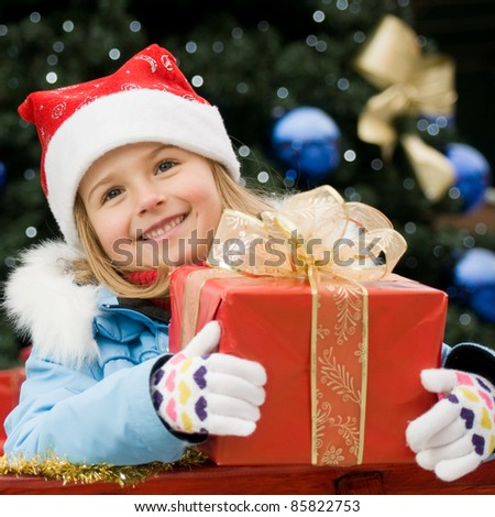 Merry Christmas - cute girl with Christmas gift  (Defocused Christmas Tree Lights) - stock photo