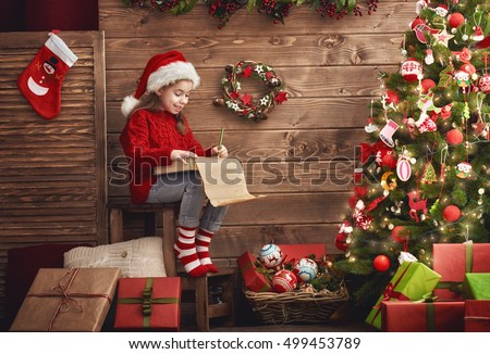 Merry Christmas! Cute little child girl writes the letter to Santa Claus.