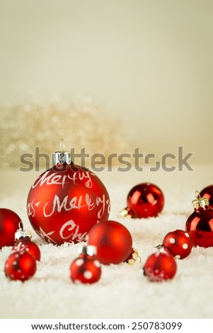 Merry Christmas festive background with a collection of different sized red baubles nestling in winter snow with focus to the largest saying - Merry Christmas - with copyspace - stock photo