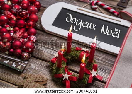 "Merry christmas greeting card with four red candles and french text: ""Joyeux Noel"". - stock photo"