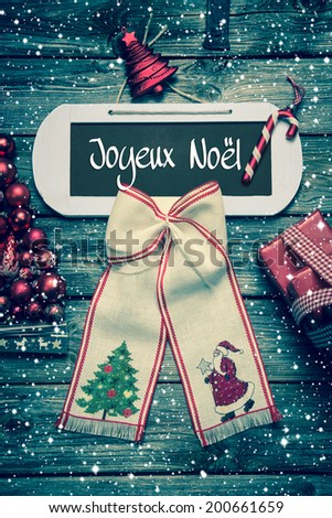 Merry Christmas greeting card with french text on wooden background. - stock photo