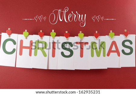 Merry Christmas greeting message across red and green letter cards hanging from heart shape pegs on a line bunting with text against a festive red background - stock photo