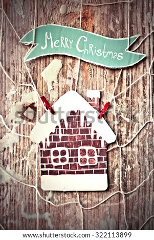 Merry Christmas greeting message on wooden background, Paper tag with strings, wishing a Merry Christmas over old wood surface and ginger bread house. Retro style Christmas background with copy space - stock photo