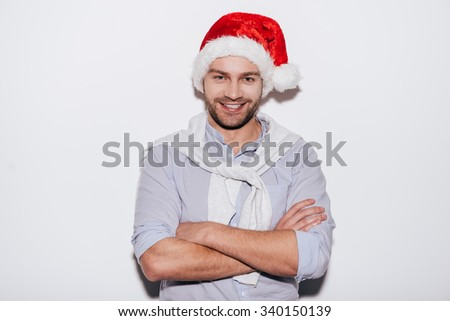 Merry Christmas! Handsome young man in Santa hat keeping arms crossed and smiling while standing against white background