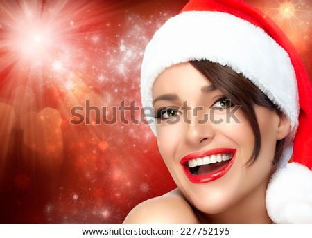 Merry Christmas. Happy Christmas girl in Santa hat with a beautiful big smile. Sensual red lips and manicure. Fashion portrait with flashing lights background - stock photo