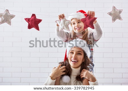 Merry Christmas! Happy mother and daughter hang a Christmas garland. - stock photo
