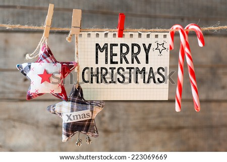 Merry christmas inscription. Merry Christmas inscription on checkered paper attach to rope with candies  - stock photo