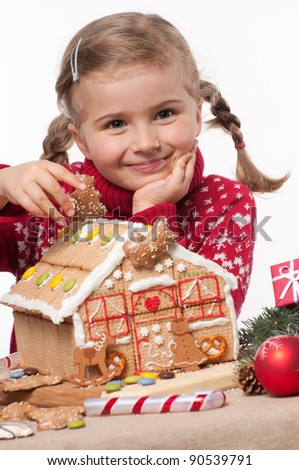 Merry Christmas - Little girl decorating Christmas cookies house - stock photo