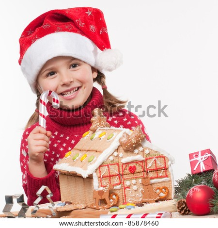 Merry Christmas - Little girl decorating oneself made Christmas cookies house