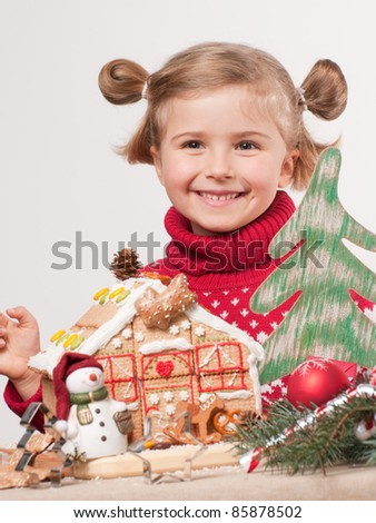 Merry Christmas - Little girl decorating oneself made Christmas cookies house - stock photo