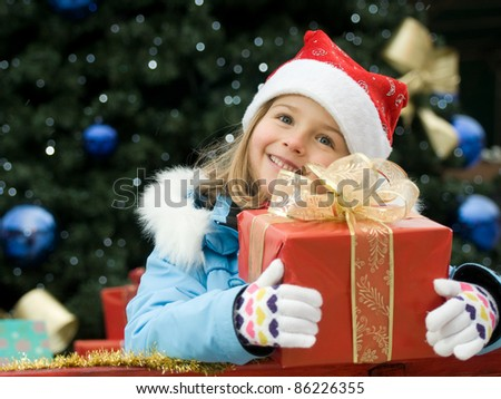 Merry Christmas - Little girl with Christmas gift - stock photo