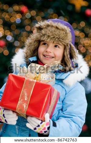 Merry Christmas - Little girl with Christmas gift - Defocused Christmas Tree Lights - stock photo