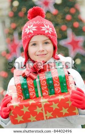 Merry Christmas - Little girl with Christmas presents - Defocused Christmas Tree Lights - stock photo