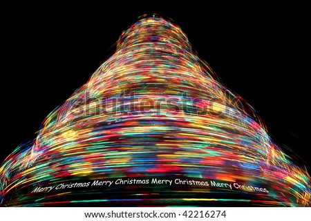 Merry Christmas - Long Exposure of Rotating Christmas Tree with Cycling Optical Fibre Lights against a black background - stock photo