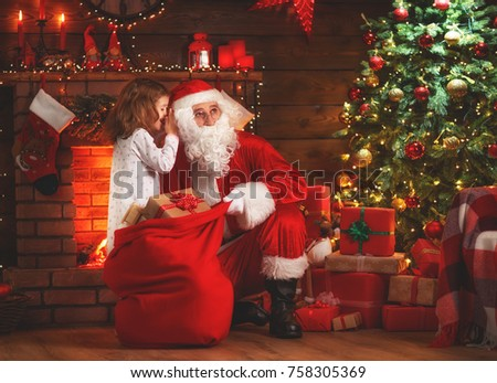 Merry Christmas! santa claus and little child girl at night at the Christmas tree