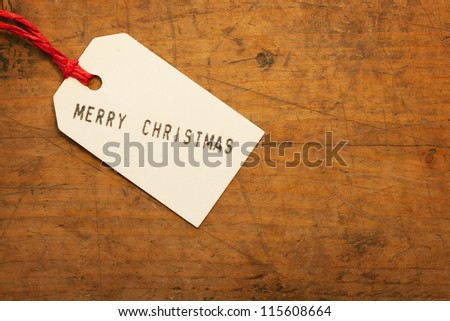 Merry Christmas tag on old wooden surface.