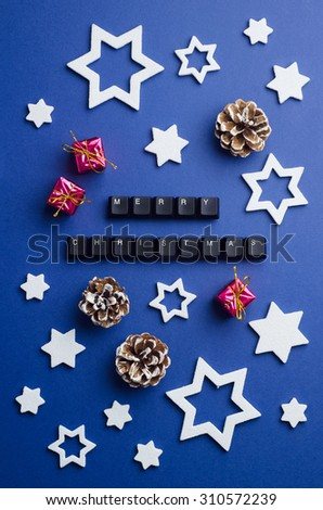 Merry Christmas text made of keyboard keys and other christmas decoration over dark blue background, above view