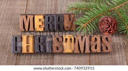 Merry Christmas text on a wooden surface with tree branch and pinecone