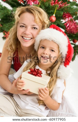 Merry christmas - woman and little girl with a present - closeup portrait - stock photo